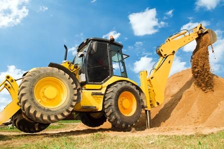 Wheel loader Excavator with backhoe unloading sand at eathmoving works in construction site photo