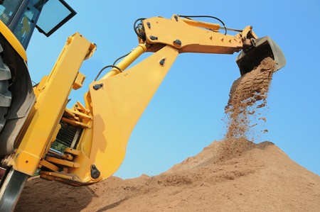 'earth mover': Wheel loader Excavator with backhoe unloading sand at eathmoving works in construction site