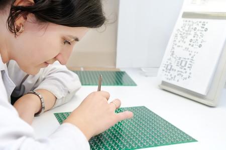 assembly: Mujer de blanco uniforme de comprobación o montaje de componentes y de chip en microcircuito integrado Foto de archivo