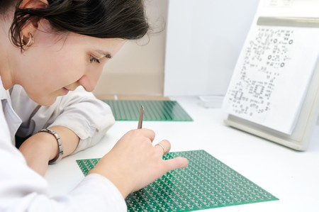 micro chip: Woman in white uniform checking or assembling components and chip on integrated microcircuit Stock Photo