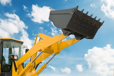 risen loader excavator scoop shovel over blue sky Stock Photo