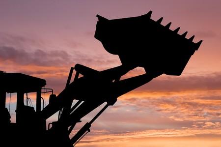 silhouette of risen loader excavator scoop shovel over scenic dawn Stock Photo - 7817923