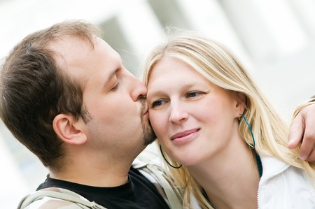 Young man kissing smiling sweetheart woman with tenderness photo