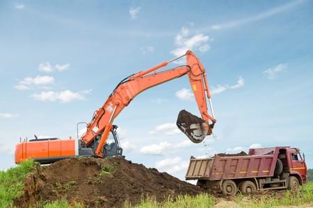 Heavy excavator loading dumper truck with sand in sandpit over blue sky photo