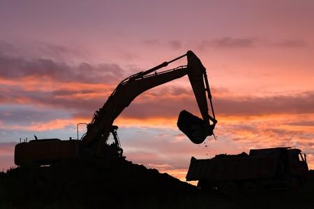 mijnbouw: Zware graaf machine dumper truck met zand in de zand bak laden bij zons opgang