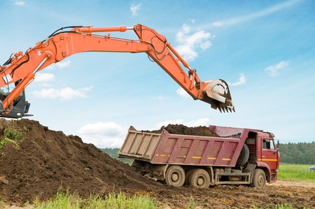 Heavy excavator loading dumper truck with sand in sandpit over blue sky photo