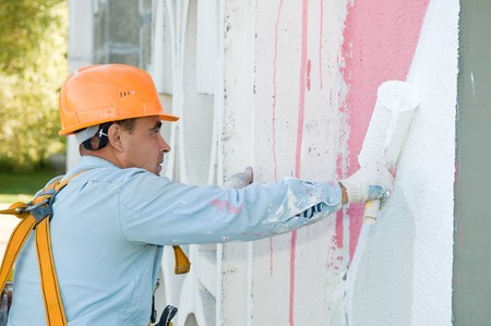 builder worker painting facade of building house with roller photo