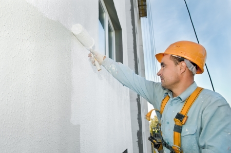 facade building: builder worker painting facade of building house with roller Stock Photo