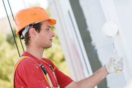 work safety: builder worker painting facade of building house with roller Stock Photo