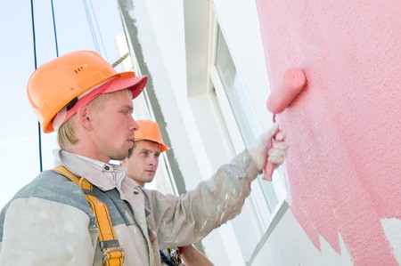 hardhat: builder worker painting facade of building house with roller Stock Photo