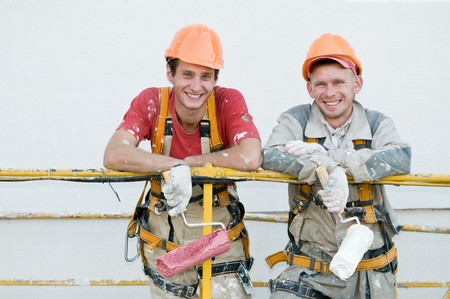 masters: Two happy builder workers  facade painters of high-rise building with rollers