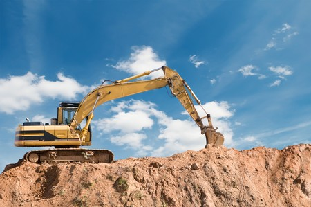 digging: loader excavator in open sand mine over scenic blue sky Stock Photo