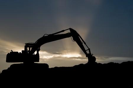 mijnbouw: silhouet van loader graaf machine scoop shovel over schilderachtige zons ondergang