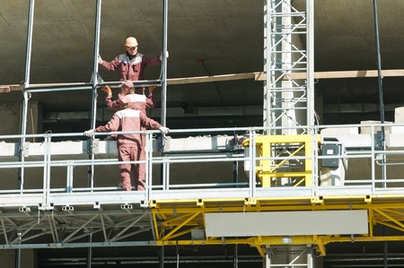 group of workers at restoration building works in mast climbing platform photo