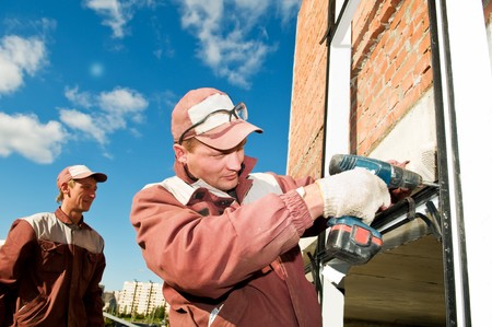 screwing: Builders laborer in work wear screwing a screw with screwdriver machine