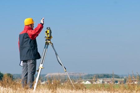 Surveyor werknemer waardoor de meting in een veld met theodoliet total station apparatuur