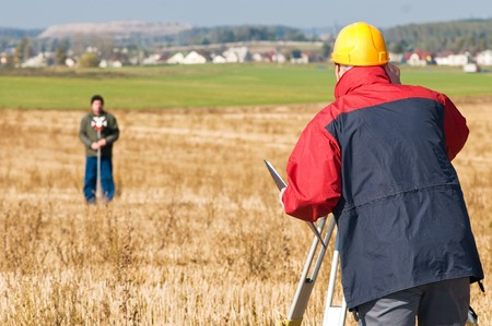 exact position: Two surveyor workers with theodolite total station equipment outdoors Stock Photo