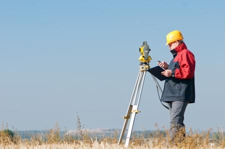 topografo: Trabajador de top�grafo haciendo de medici�n en un campo con el equipo de estaci�n total de teodolito