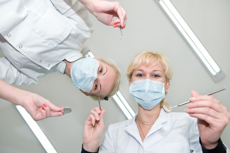 bending over: two happy dentist with dental equipment tools preparing for treatment and bending over patient
