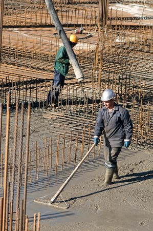 two builder workers during concrete works at construction site. Levelling and pouring Stock Photo - 8207153
