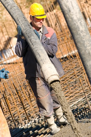 builder worker aiming pump tube during concrete pouring process at construction site