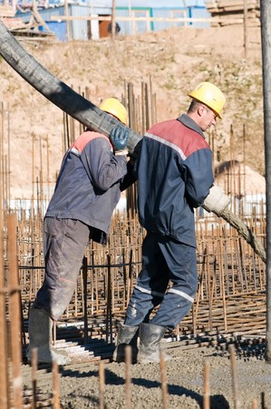two builder workers aiming pump tube during concrete pouring process at construction site photo