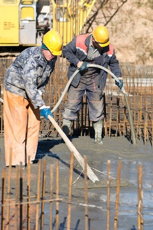 vibration machine: two builder workers during concrete works at construction site. Levelling and vibration