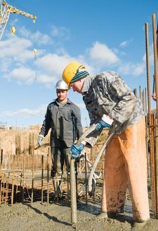 vibration: builder laborers works on construction site. Concrete pump and Vibration