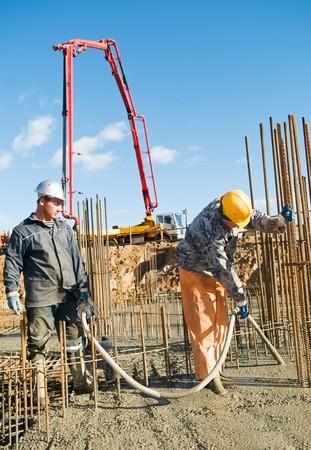 concrete pump: builder laborers works on construction site. Concrete pump and Vibration