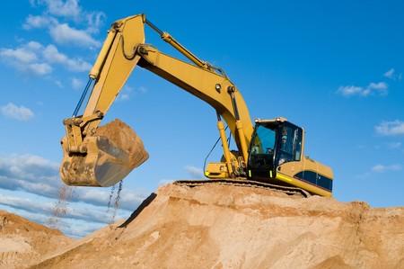 equipos: máquina de cargador de excavadora durante el movimiento de tierras trabaja al aire libre en el sitio de construcción  Foto de archivo