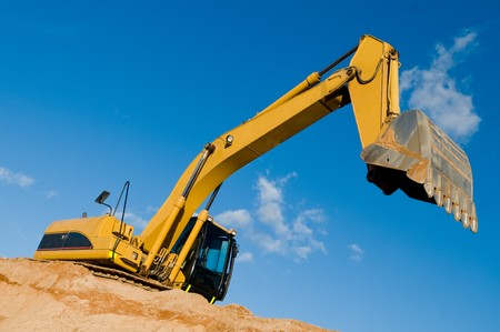 backhoe: excavator loader machine during earthmoving works outdoors at construction site