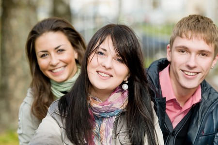 Group portrait of three smiling cheerful students outdoors in autumn photo