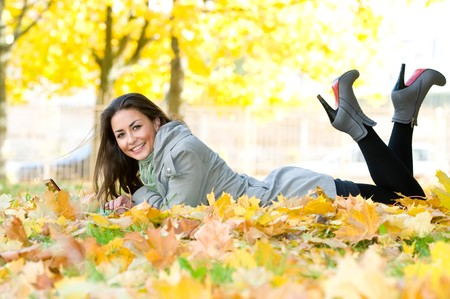 One young pretty student girl in yellow autumn leaves with computer laptop photo