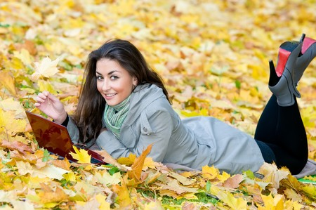 One young pretty student girl in yellow autumn leaves with computer laptop Stock Photo - 8207098