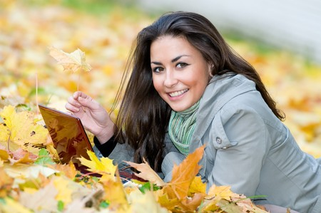 One young pretty student girl in yellow autumn leaves with computer laptop Stock Photo - 8207057