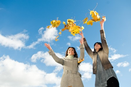 leafage: Two happy student girls celebrates autumn by throwing up yellow leafage over blue sky