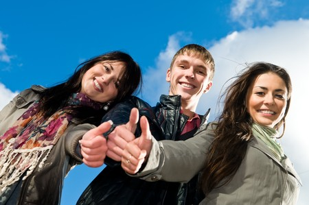 Three students standing over blue sky with thumbs up. Lower point of view photo