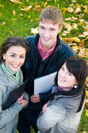 Three students standing with clipboards in park on yellow autumn leaves Upper point of view photo