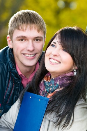 Group portrait of two smiling cheerful students outdoors in autumn photo