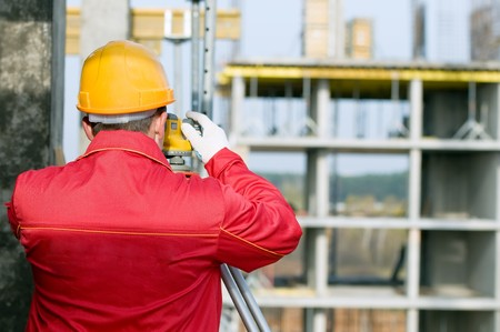 optical equipment: builder surveyor working with optical equipment level at construction site Stock Photo