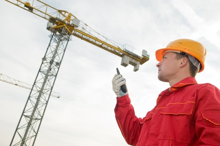 transmitter: builder worker in uniform and helmet operating with tower crane by portable radio station transmitter