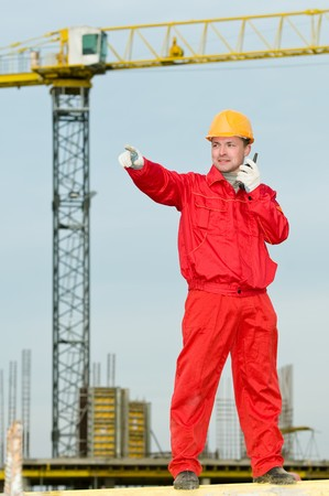 builder worker in uniform and helmet operating with tower crane by portable radio station transmitter photo