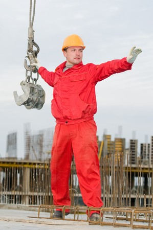 rigger: rigger builder in uniform and helmet operating with straps at construction area