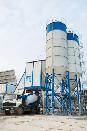 to plant structure: Stationary Concrete Batching Plant unloading cement into mixer truck Stock Photo