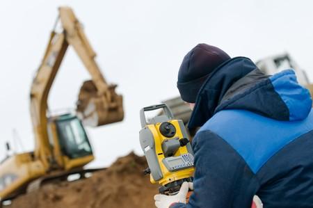 teodolito: trabajador de topógrafo con teodolito de dispositivo de equipo de geodesia en tierra agrimensura al aire libre Foto de archivo
