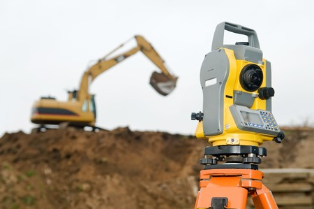 work station: Surveyor equipment theodolite on tripod at building area in front of working construction machinery loader Stock Photo