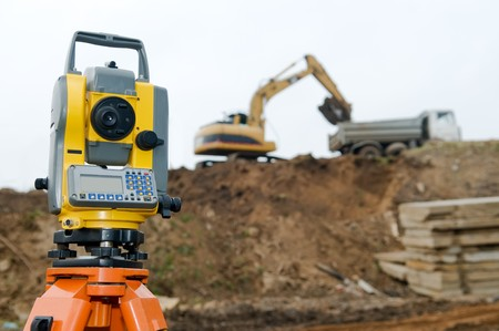 Surveyor equipment theodolite on tripod at building area in front of working construction machinery loader Stock Photo - 8202898