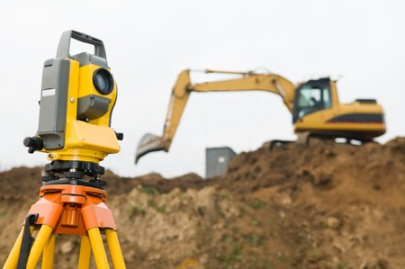 leveling: Surveyor equipment theodolite on tripod at building area in front of working construction machinery loader Stock Photo