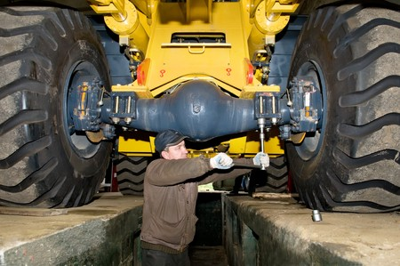 industrial machinery: repairman worker screwing nuts of axle assembly in heavy wheel loader  Stock Photo