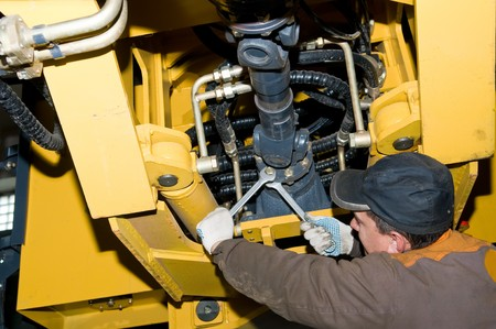 job engine: repairman worker screwing nuts of axle assembly in heavy wheel loader  Stock Photo